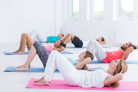 Group of diverse people doing sit-ups in exercise fitness class Stock fotó