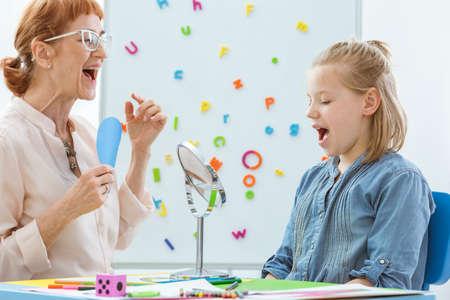 Conseiller scolaire pendant la rééducation de la parole et de la langue avec une petite fille Banque d'images - 82516172