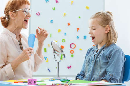 School counselor during speech and language rehabilitation with small girl Foto de archivo