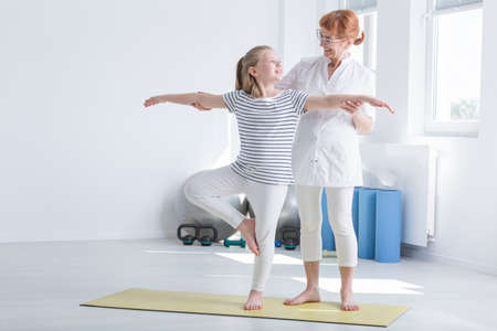 Child exercising with positive female physiotherapist in bright gymnastics room
