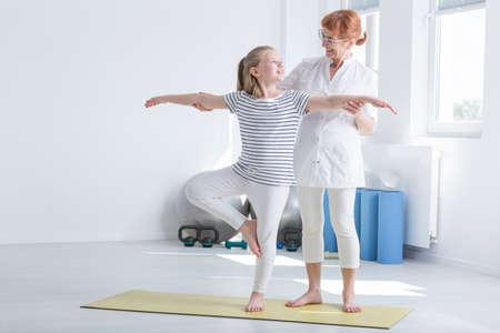 Kind oefenen met positieve vrouwelijke fysiotherapeut in felle gymnastiekkamer Stockfoto