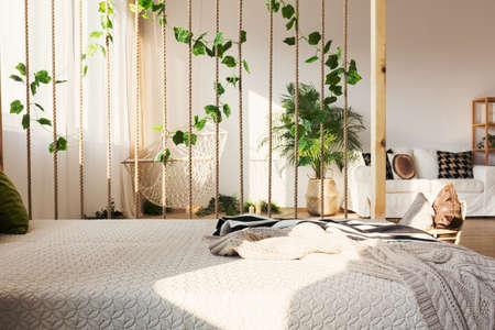 元のアパートでエレガントなベッドの横にロープやツタの装飾的な部屋ディバイダーを鼓舞 写真素材