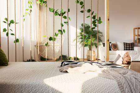 Inspiring rope and ivy decorative room divider next to elegant bed in original apartment