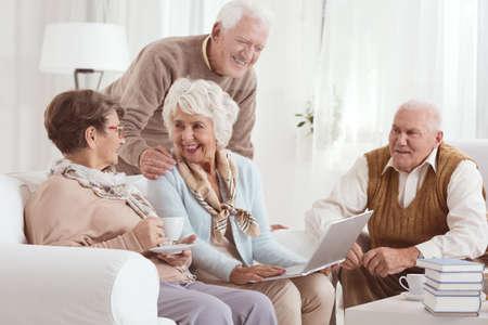 Vriendelijk gesprek van bejaarde buren die tee drinken en een laptop gebruiken