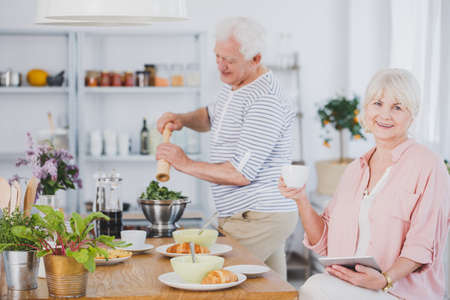 Senior woman with a cup of coffee and a man making salad in the kitchen