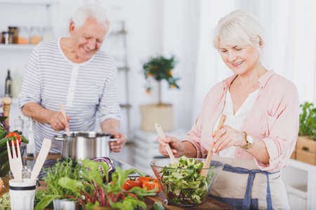 Senior man and woman preparing food in the kitchen Stockfoto