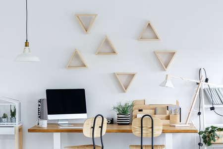 Skandinavische studiewerkruimte met computer, houten bureau en witte muur