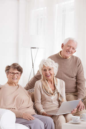 Three elderly adults using a laptop at a day-care center