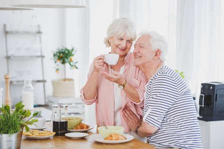 Oudere man en zijn vrouw met een witte kop koffie in de keuken