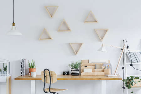 White scandi interior with wooden desk, triangle shelves and plants