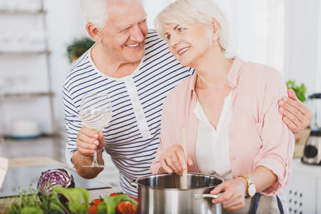 Senior couple cooking together in the kitchen Reklamní fotografie - 82873136