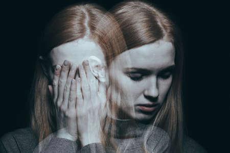 若い女の子の彼女の不況のピークに達した後彼女の手で彼女の顔をカバー