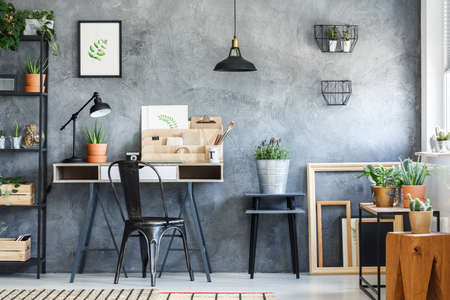 Empty frames, potted plants and poster in vintage craft studio 스톡 콘텐츠