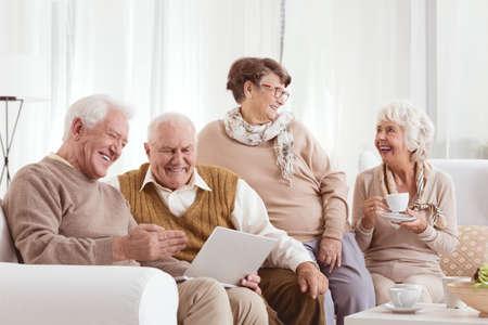 チャットとラップトップを使用しての保育所でリラックスした高齢者の友人