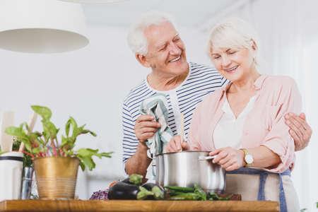 台所のスープを作るシニア カップル