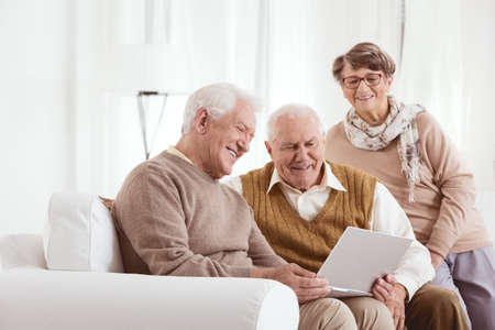 Elderly man showing his new laptop to his family at retirement home Zdjęcie Seryjne