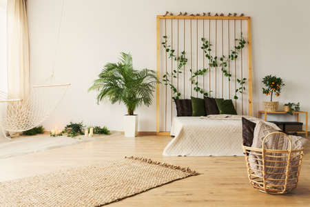 Stylish natural bedroom with simple hammock and plants