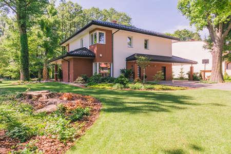 테라스가있는 현대 집에서 화창한 정원에서 봅니다.
