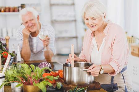 Senior vrouw koken met man op de achtergrond