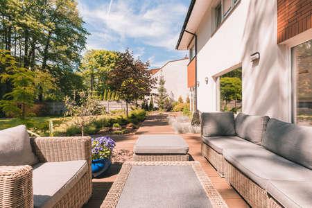 Outdoor garden wicker furniture in sunny patio of modern house