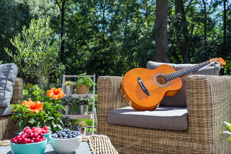Shot of a wicker garden armchair with the guitar on Stock fotó