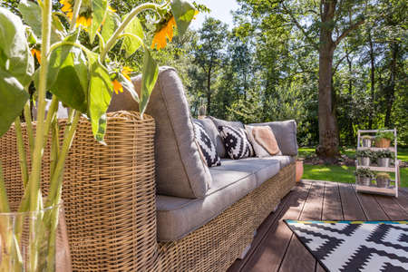 Close shot of a sunflowers vase located close to the garden couch with pillows Stock fotó
