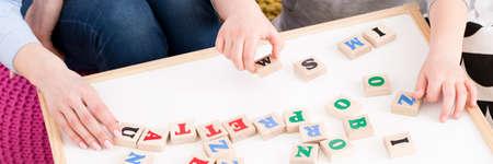 Close-up van jong meisje dat het woord van houten brieven plaatst Stockfoto