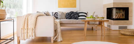 White knit blanket lying on the corner sofa in the living room with fireplace Stock Photo