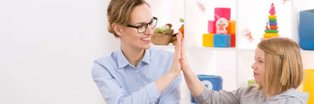 compensatory: Young teacher giving little students high five for good job Stock Photo