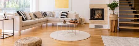 Houten trap in moderne woonkamer met hoekbank en open haard Stockfoto - 82837138