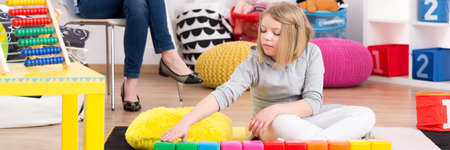 compensatory: Young girl on psychotherapy playing with colorful blocks