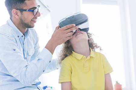 Teacher shows the girl the VR glasses during extracurricular IT classes, modern school concept