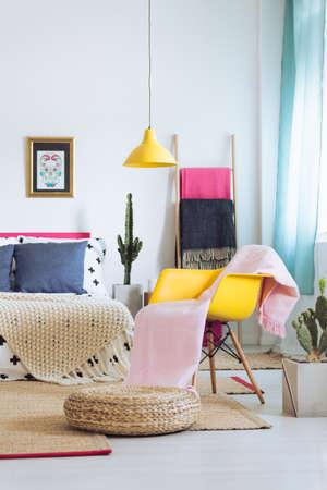 黄色のランプ、アームチェア、頭蓋骨のポスターでスタイリッシュな明るい寝室