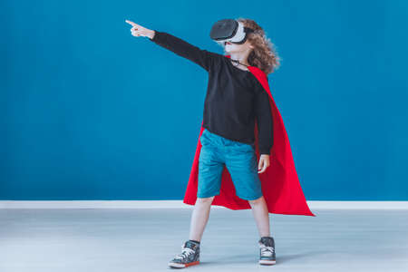 Happy boy dressed up as a superhero feels in the game while using VR glasses Stock Photo