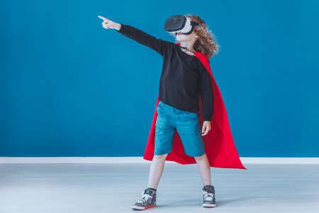 VR 안경을 사용하는 동안 게임에서 슈퍼 히어로 느낌으로 행복 소년 차려 입다.