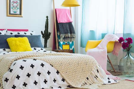 Bett Decken Konzept : Rosa decke auf gelbem stuhl in der nähe von blauem glasvase mit