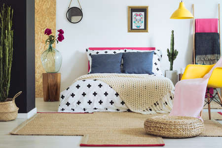 Vividly multicolored bedroom with white wall in folk ethnic style Stock Photo
