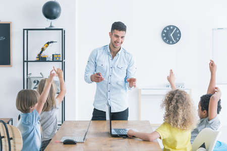 아이들은 선생님 집에서 컴퓨터 과학 수업을하는 동안 손을 들어 듭니다. 현대 학교 개념
