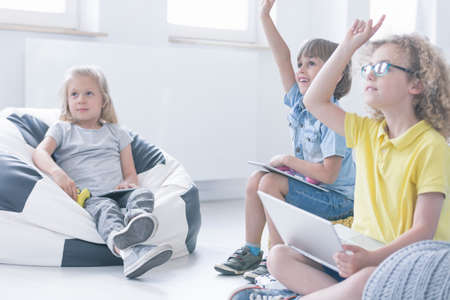 Girl is sitting in a black and white pouf during an interesting programming lesson modern teaching concept Imagens