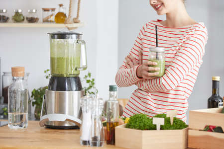 Woman drinking just blended smoothie from fresh veggies Stock fotó