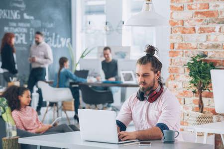 공동 창조적 인 공간에서 자신의 노트북에서 작업하는 젊은 남자