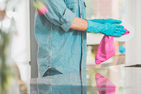 Woman in jeans shirt wipes plate with pink towel in modern kitchen Stock Photo