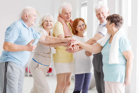 Team of happy active seniors gathering hands together before the training