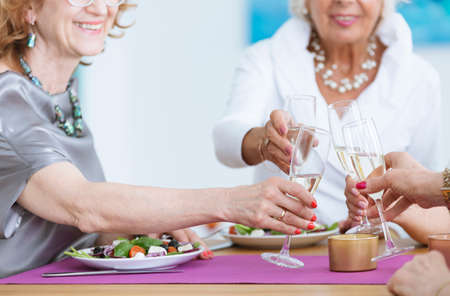 Smiling women with glasses of champagne making a toast Stock Photo