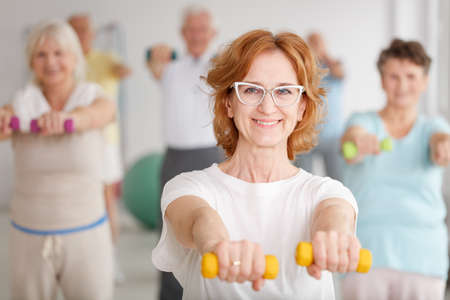 Smiling lady with glasses exercising with yellow dumbbells at group training
