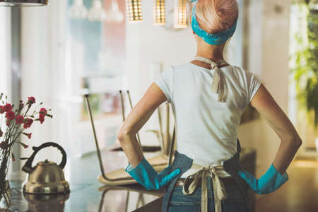 Happy housewife stands with hands on hips and looking at clean apartment Stock Photo