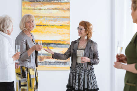 Four happy senior women having fun at the art gallery