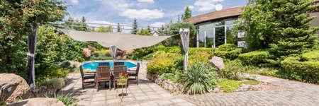 ガーデン テラスのキャノピーと木製の快適な庭の家具