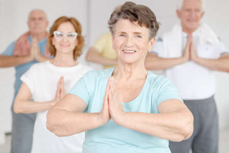 Smiling active woman exercising at yoga classes together with her friends