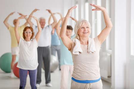 運動する前にウォーム アップ中に幸せな高齢者のグループ